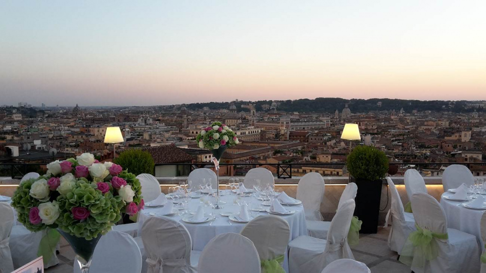 Wedding dinner set-up ,elegant tables and coloured fresh flowers con the tables in panoramic terrace