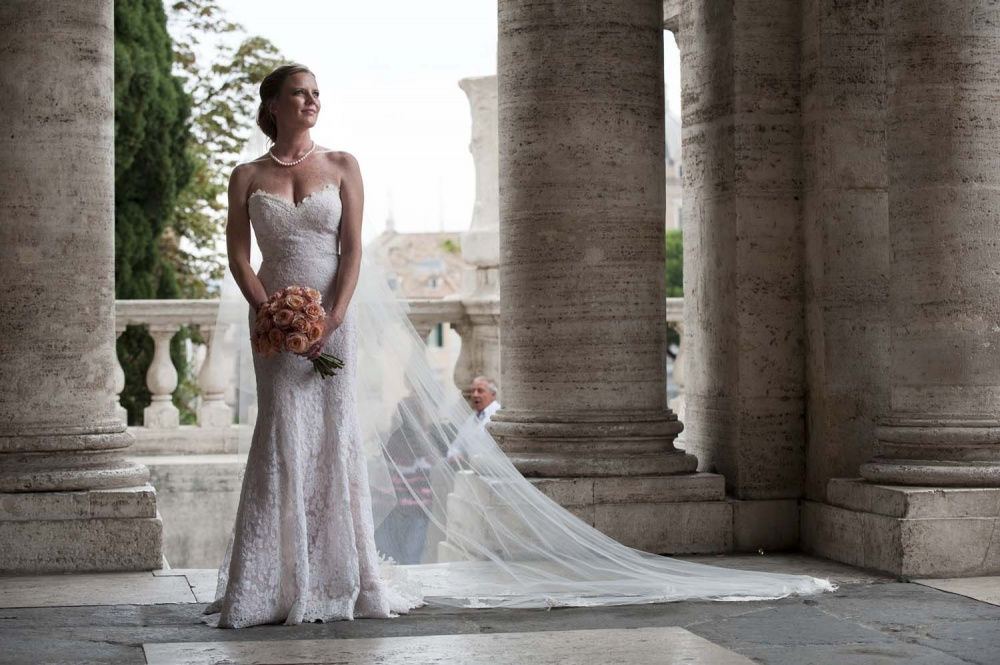 Bride with long dress and a peach color bouquet in a portrait in Rome