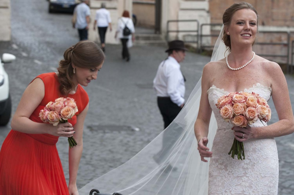 Bridesmaids helping the bride before the ceremony in Rome with peach color bouquet