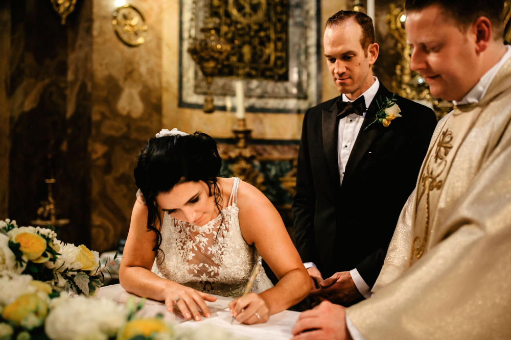 Bride while signin the wedding papers on altar table finely decored with flowers