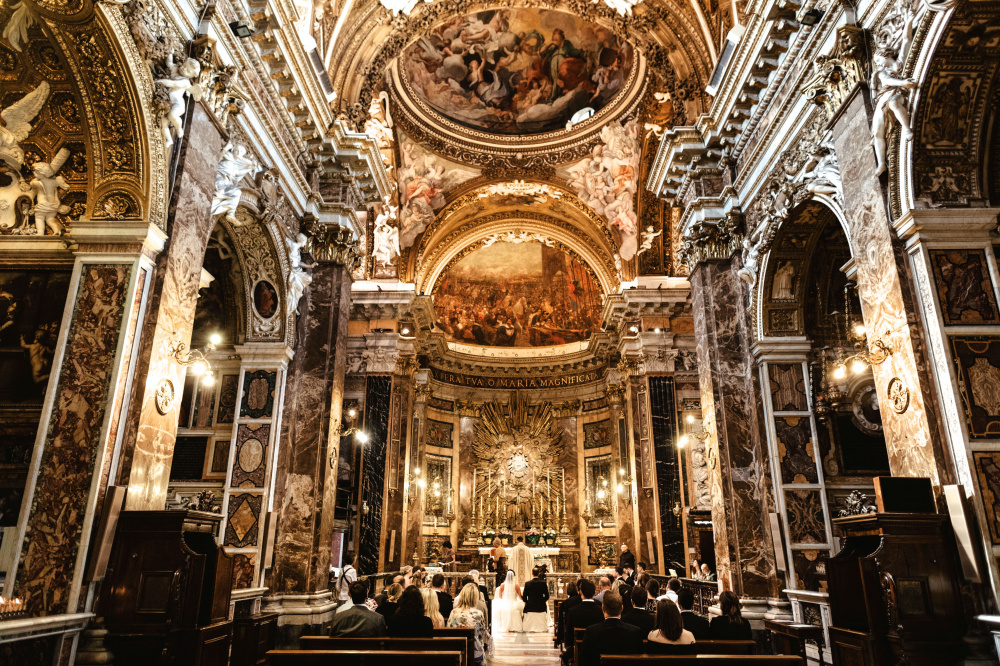 A view from the main entrance of a beautiful baroque ceremony catholic church richly adorned