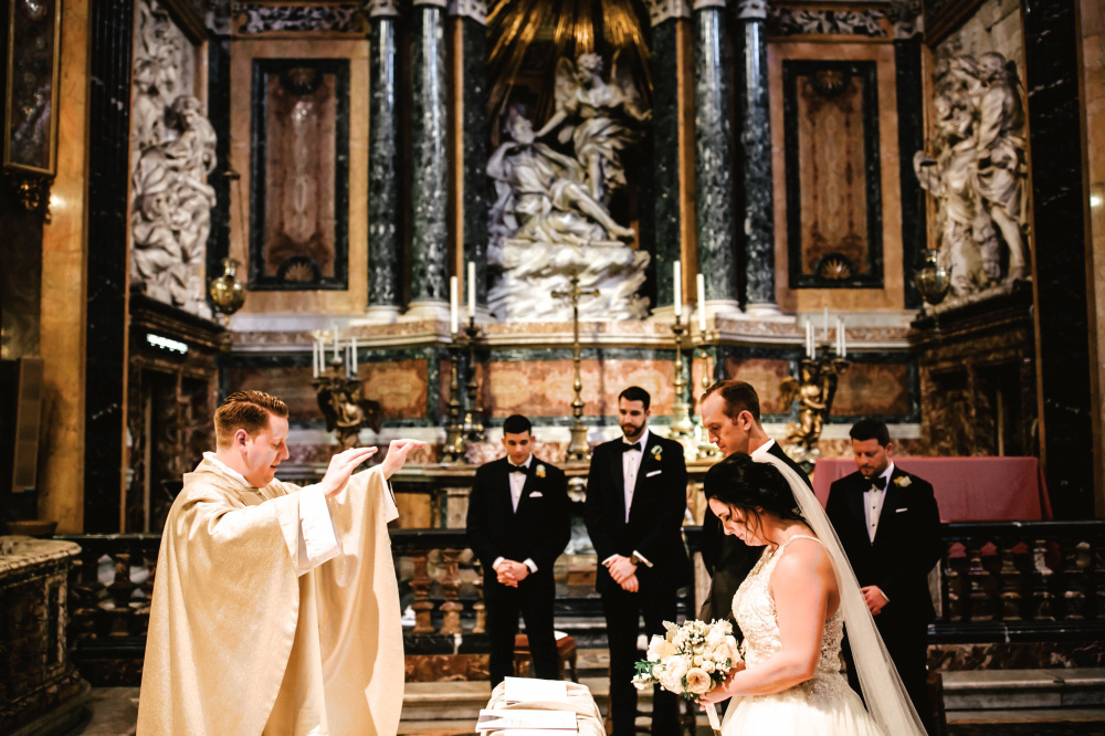 Blessing moment during wedding ceremony with bernini's sculpural masterpiece on the back