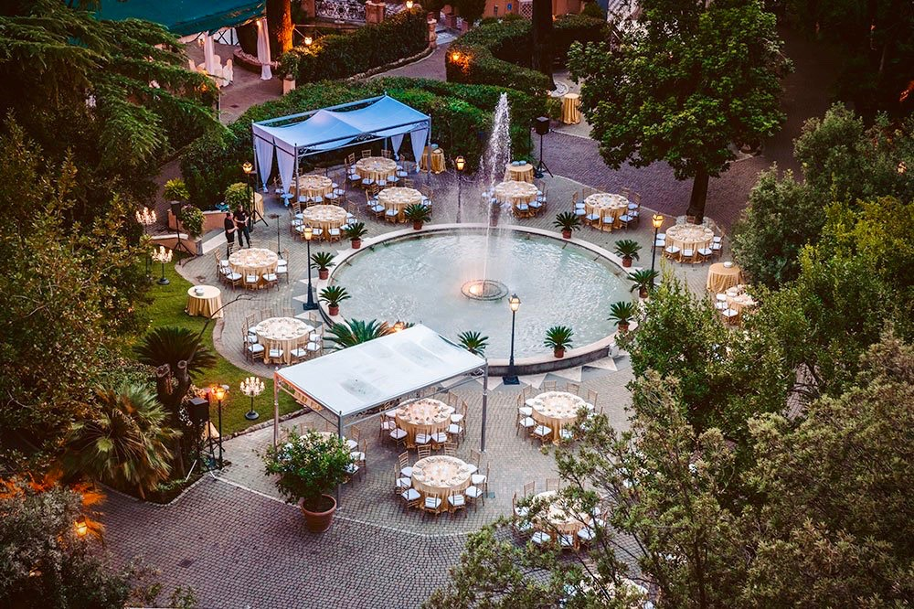Aerial view wedding set-up with elegant round tables in the palace's verdant gardens in Rome
