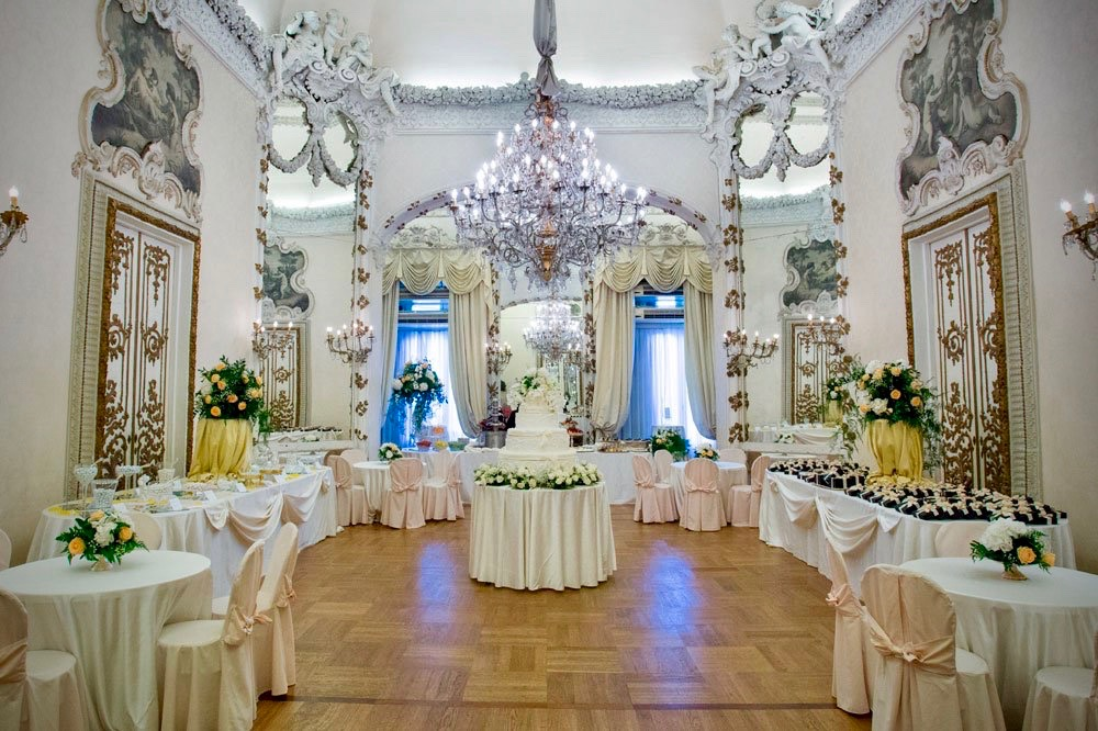 elegant and rich wedding hall in white colours, mirrors, beautiful chandeliers for wedding dinners