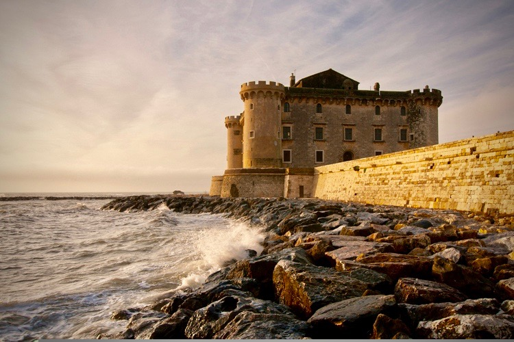 An amazing view of the castle by the sea coast at sunset, a super romantic location,
