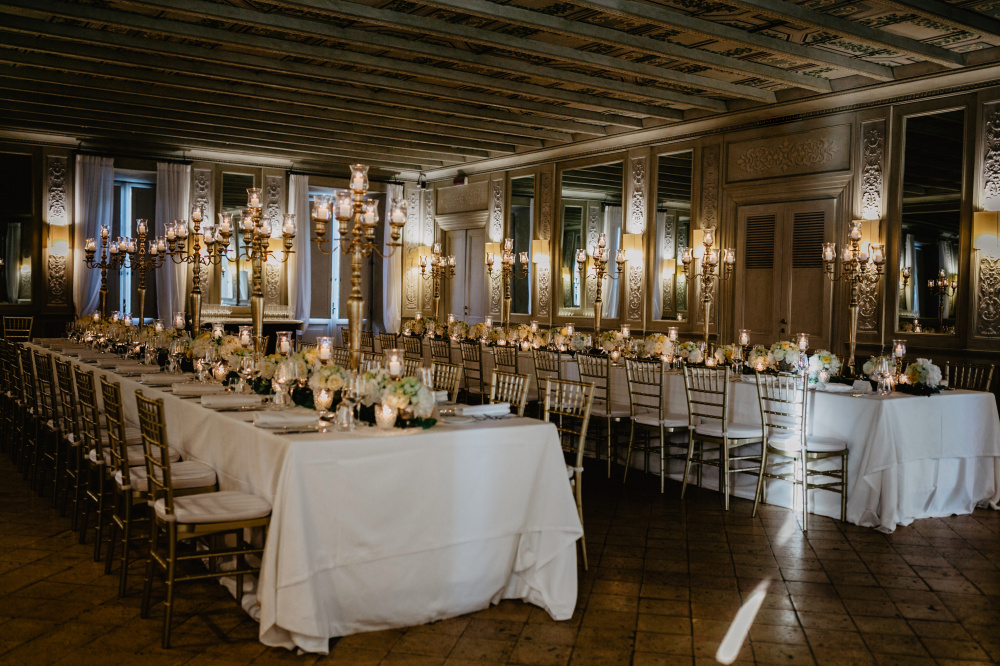 wedding dinner set-up with rectangular tables with gold candelabras in a ballroom in Rome