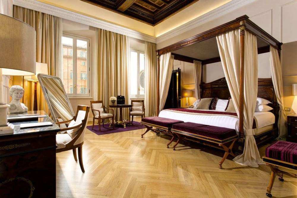 charming suite for newly married couples with canopy bed beige and burgundy decors and wood flloor