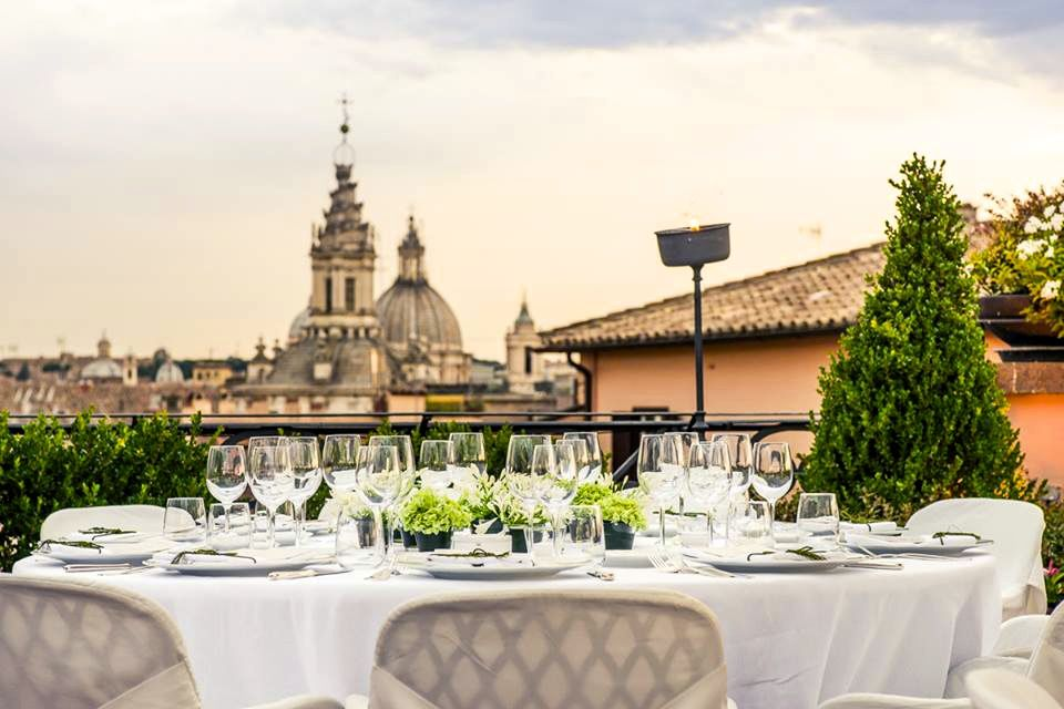 An elegant lunch table set on the roofterrace of luxury wedding hotel with stunning view over Rome