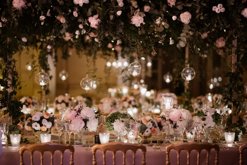 Wedding decor with hanging candles, cascading greenery and pink and ivory flowers