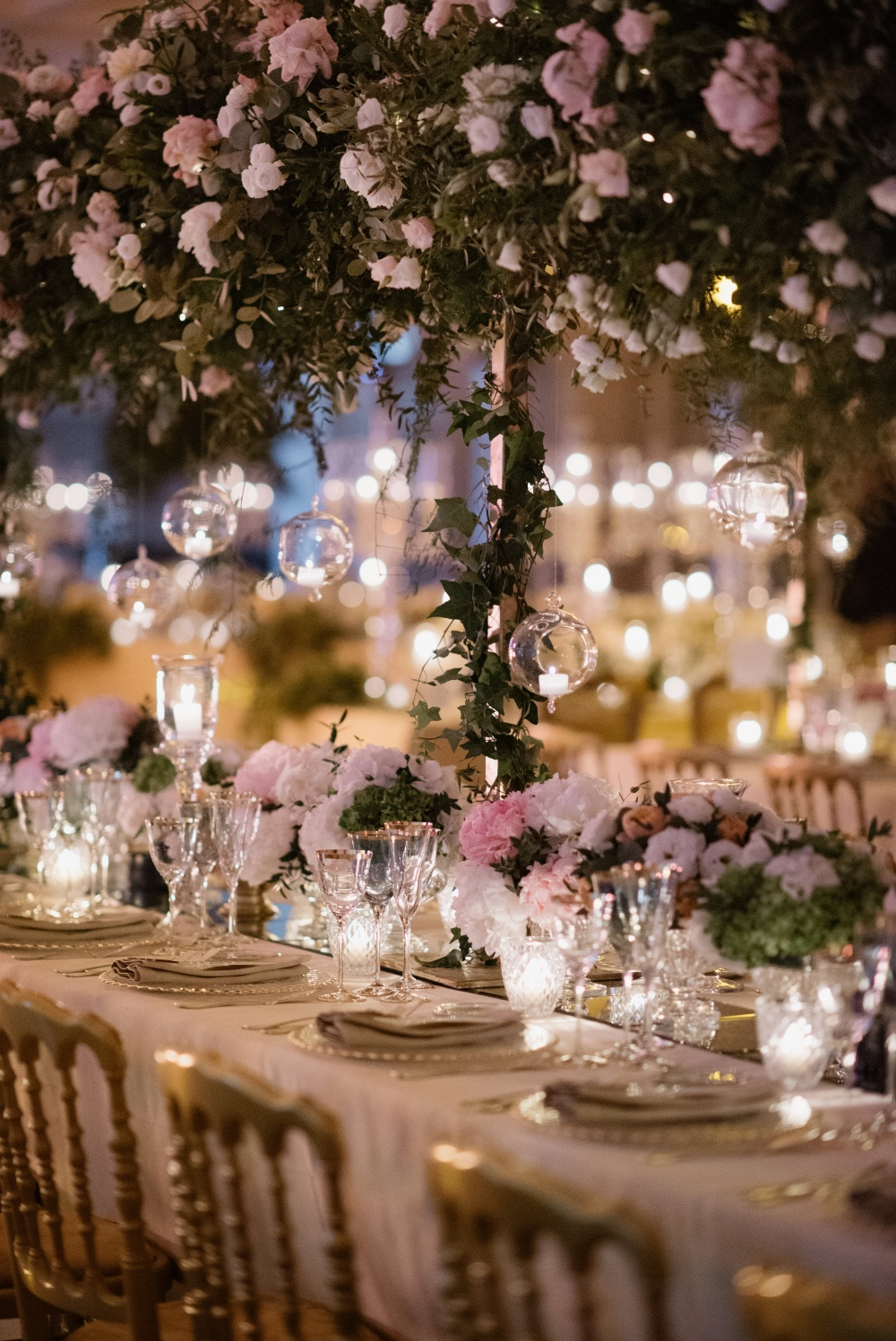 Table setting with ivory and pink flowers, hanging candles and cascading greenery