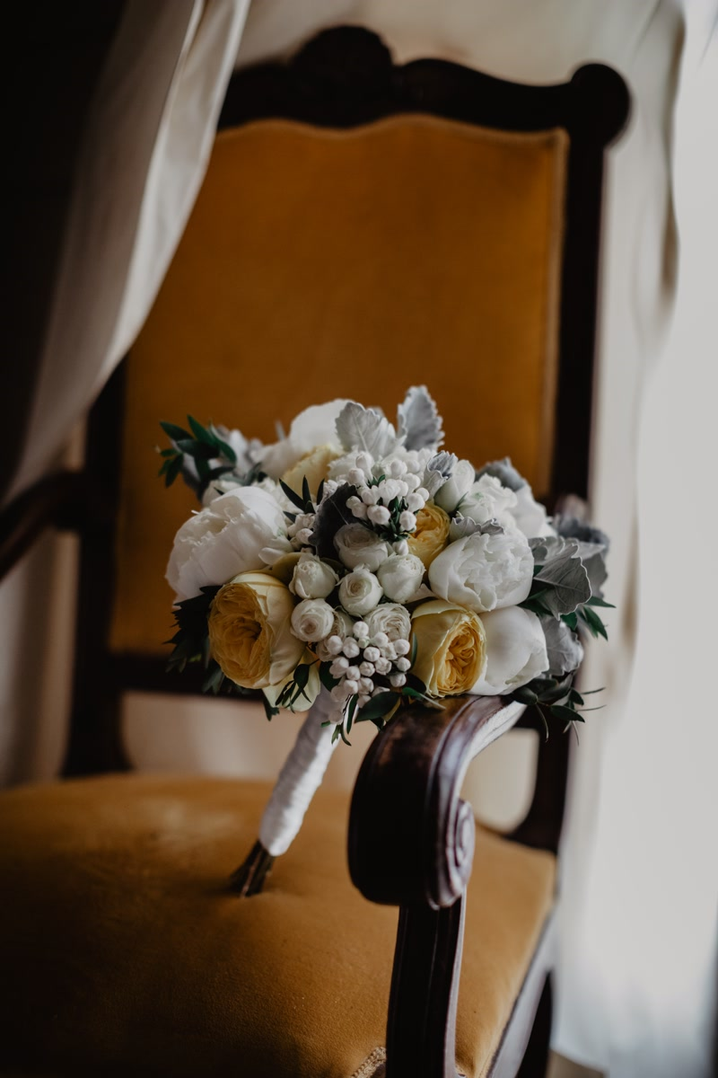 White and yellow bridal bouquet on an orange armchair