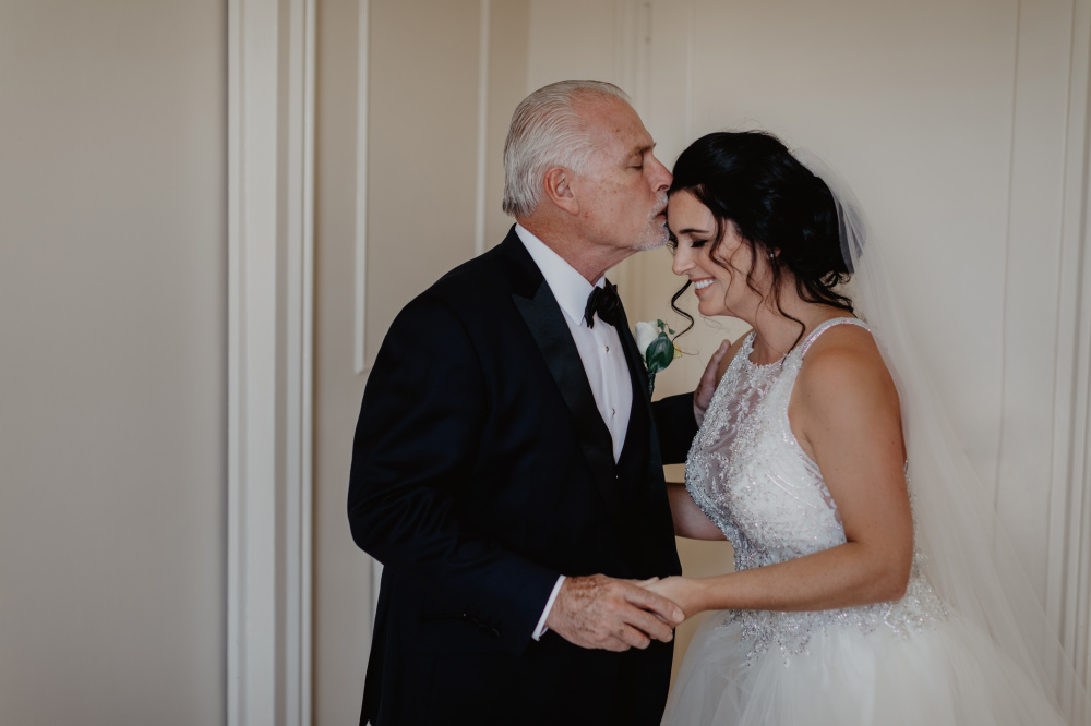 Father of the bride kisses his daugther