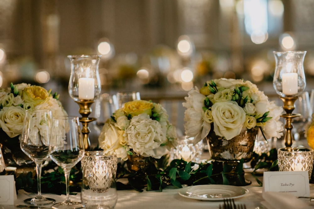 White and yellow flowers with candles as table decor