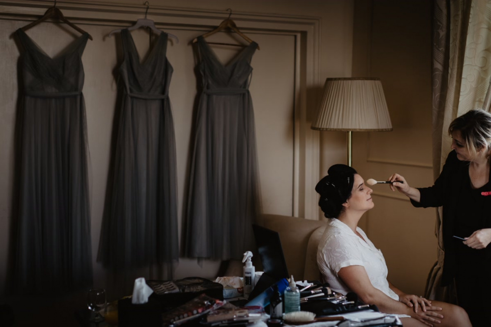The bride is getting ready with the make up artist and three grey dress
