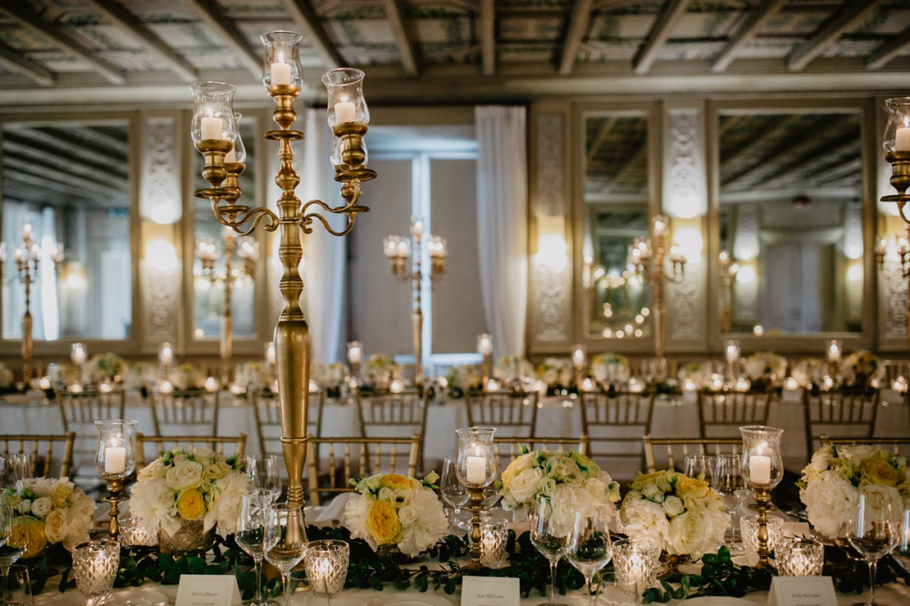 Gold candelabras, white and yellow flowers and gold chair as wedding decor in Rome