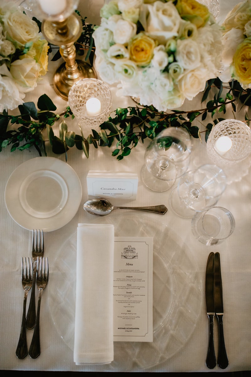 Printed menu, transparent glass chargers and white flowers as wedding table decor in Rome