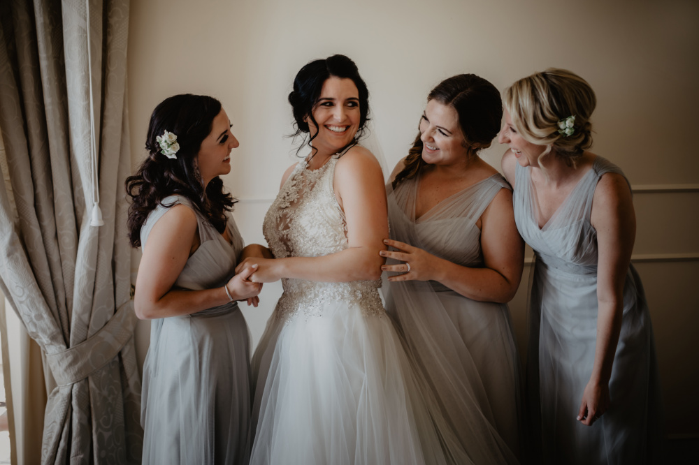three bridesmaids and the bride with white and light grey dresses