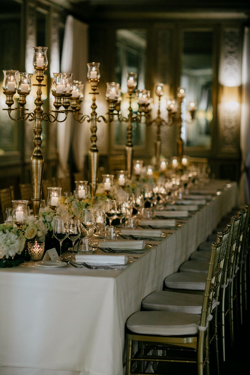 Table with gold candelabras, white table clothes, gold chairs and white and yellow flowers as wedding decor in Rome