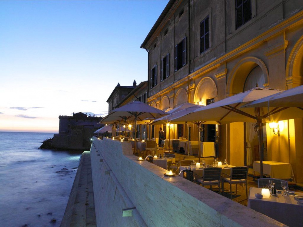 night view restaurant's terrace over sea old castle as background for romantic pre-wedding dinner