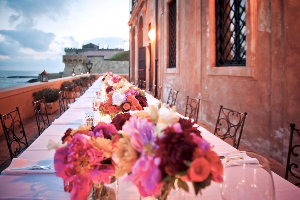 amazing long wedding table along the terrace over the sea with colourful fresh flowers at sunset