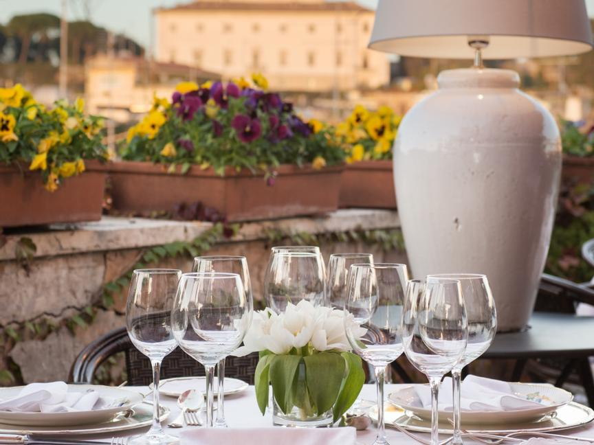 Romantic dinner table set for intimate dinner on a rooftop garden with rome on the background
