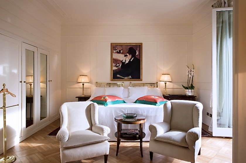 Suite's sleeping room, white and gold colour, painting over the bed,2 white single sofas, wood floor