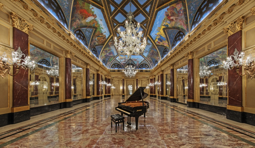 Baroque style ballroom of a luxury hotel in Rome with piano and chandelier
